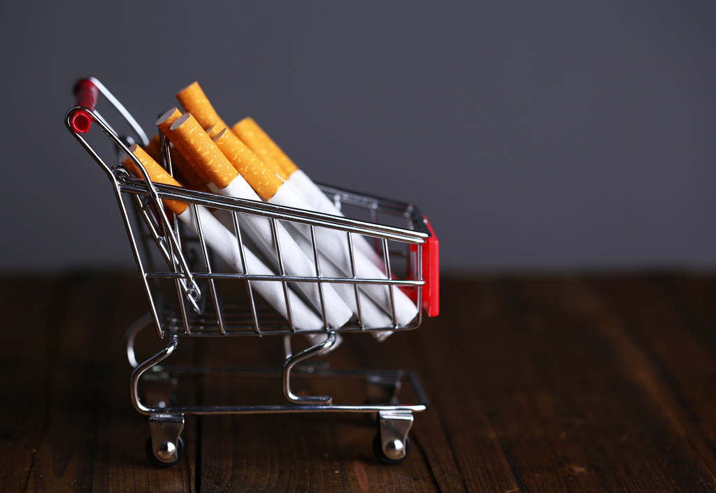 Cigarettes in shopping cart on wooden table on dark gray background