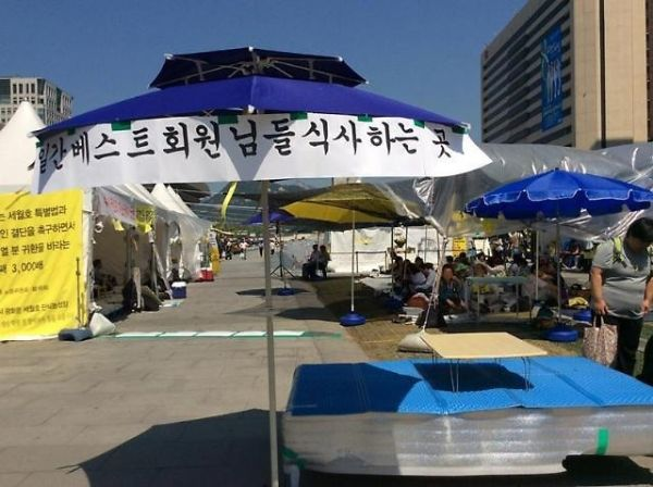 Ultra-right camp members ate foods under parasols installed for them by none other than the National Task Force at the Gwanghwamun Gate who are responsible for the hunger strike protesters for the Sewol ferry. (image: the National Task Force)