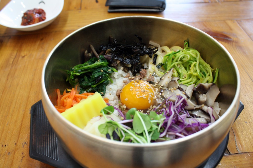 "Bibimbap is a signature Korean dish. The word literally means ""mixed rice"". Bibimbap is served as a bowl of warm white rice topped with namul and gochujang, soy sauce, or doenjang. (image: Joamm Tall/flickr)"