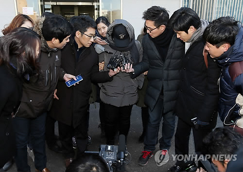 A daycare teacher accused of assaulting a 4-year-old girl which caused national uproar is answering questions surrounded by reporters. (image: Yonhap)