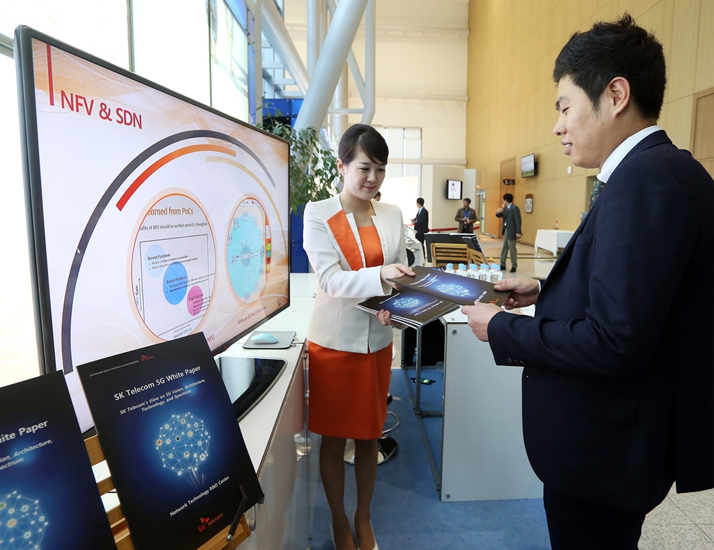 A employee of SK Telecom is introducing a white paper on 5G to visitors at the company's booth during 5G Global Summit, an international 5G conference, held in Busan last year. (image credit: SK Telecom)