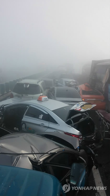 Ruined cars are entangled with each other in a thick fog after a chain collision involving about 100 vehicles on Yeongjong Grand Bridge in Incheon, west of Seoul, on Feb. 11, 2015. Firefighters said two people were killed and more than 30 injured. (image: Yonhap)