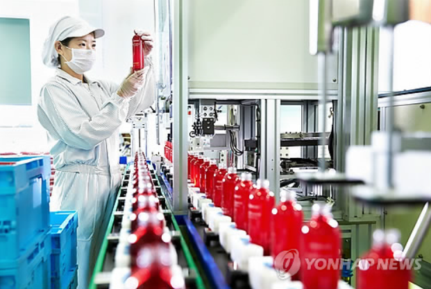 An employee at Amore Pacific, a South Korean cosmetic maker, examines a sample at a factory in Shanghai. (Image courtesy of Yonhap)