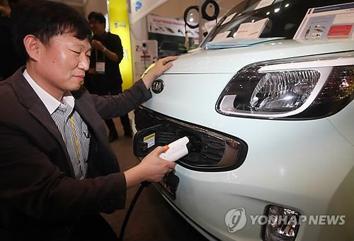 An official from local electric car charger manufacturer Power Cube tries out a mobile smart charger on March 6, 2015, during the second International Electric Vehicle Expo held on Jeju Island, South Korea. (image: Yonhap)