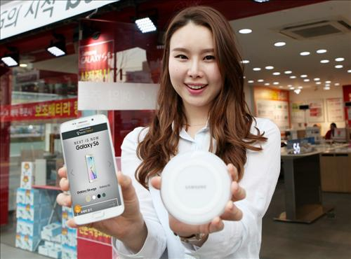 A model holds up the Galaxy S6 on March 30, 2015, which will be available for preorders by South Korean mobile carriers starting April 1. The official sales will start on April 10. (image: SK Telecom)