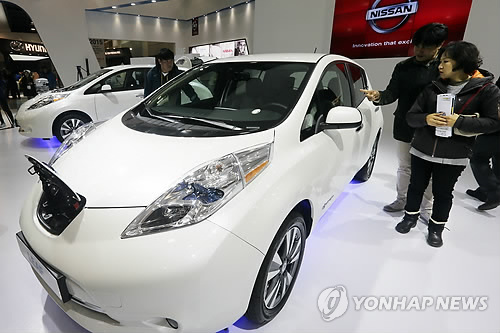 Visitors at the International Electric Vehicle Expo take a look at Nissan's Leaf hatchback electric car. (image: Yonhap)