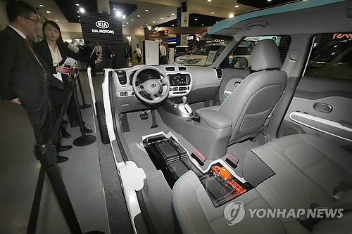 Visitors at the International Electric Vehicle Expo take a look at the interior structure of an electric car exhibited at a booth. (image: Yonhap)
