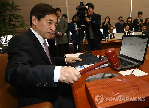 Bank of Korea Gov. Lee Ju-yeol bangs the gavel at the BOK headquarters in Seoul on March 12, 2015, to preside over a monthly policy board meeting. The board slashed the base rate to a record low of 1.75 percent, pressed for policy efforts to boost growth and inflation in Asia's fourth-largest economy. The rate cut is the first since October, when the Bank of Korea (BOK) brought down the rate to a record-matching low of 2 percent. (image: Yonhap)