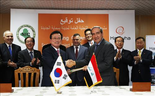 Hanwha Engineering & Construction President and CEO Lee Keun-po (L) shakes hands with Dr. Sami al Araji, head of Iraq's National Investment Commission, after signing a US$2.12 billion deal to build social infrastructure as part of the Bismayah New City Project in Iraq on April 5, 2015. (image: Hanwha E&C)