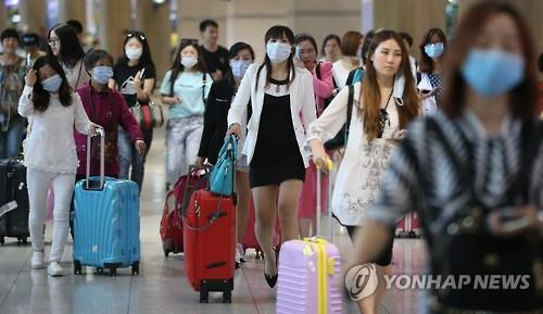 Foreign tourists wear masks upon their arrival at Incheon International Airport on June 2, 2015, after South Korea reported two deaths from the Middle East Respiratory Syndrome. (image: Yonhap)
