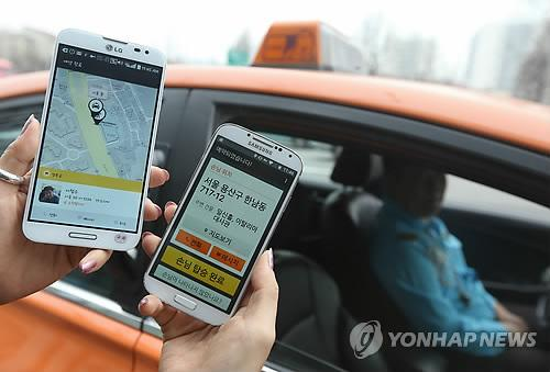 Users demonstrate the KakaoTaxi application in this file photo taken on March 31, 2015. Daum Kakao Corp. on July 6 said it plans to launch a charge-based luxury taxi-hailing service later this year, riding the popularity of its existing free app. (image: Yonhap)