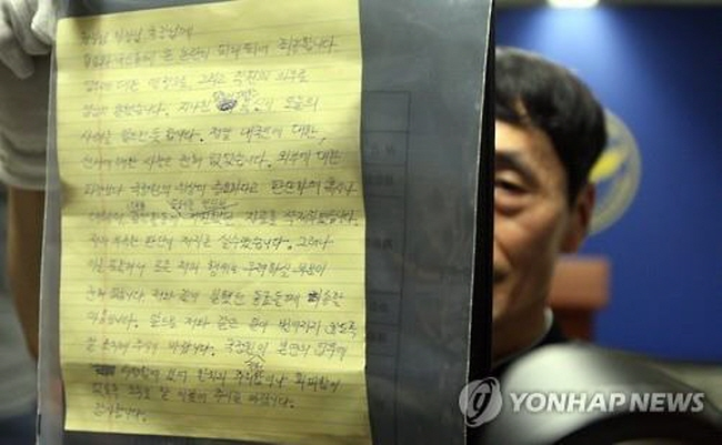 An official at Yongin Dongbu Police Station in Yongin, South Korea, on July 19, 2015, holds up a page of the will left by a National Intellgence Service employee who was found dead the previous day. (Yonhap)