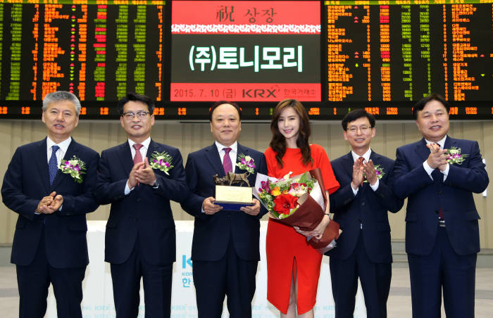 Tonymoly, a mid-end cosmetic brand, holds a ceremony to celebrate the listing its shares in the main KOSPI market on July 10, 2015, along with officials of the Korea Exchange. (image: Korea Exchange)