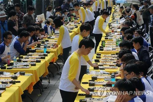 Baduk boards and rows of tables and chairs took over the sidewalk of Sejongro, next to Gwanghwamun, setting the stage for an epic 110 versus 1,300 Baduk (game of Go) match. (Image : Yonhap)