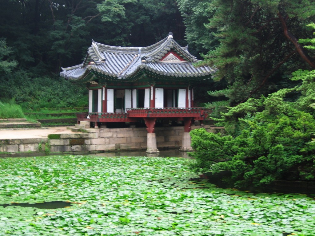 A small colorful wooden pavilion on a pond covered with lotus leaves (image courtesy of Wikipedia)