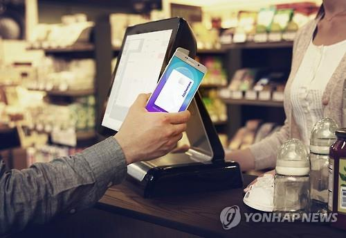 A user demonstrates how to use Samsung Pay in this file photo released by Samsung Electronics on Aug. 20, 2015. More than half of the smartphones sold wordwide will boast near field communication (NFC), a key technology in mobile payment, in 2016, a report showed on Sept. 15, which may cause Samsung to lose steam with its magnetic-backed tool. (Image : Yonhap)
