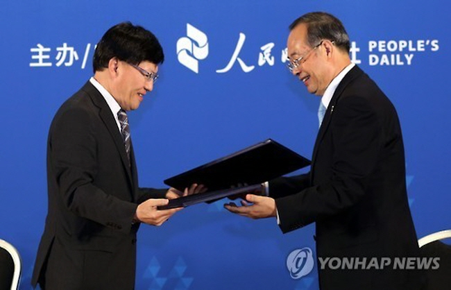 Cho Bock-rae (L), managing director for content convergence of Yonhap News Agency, and Yang Zhenwu, president of the People's Daily, exchanging a memorandum of understanding on news cooperation. (image: Yonhap)