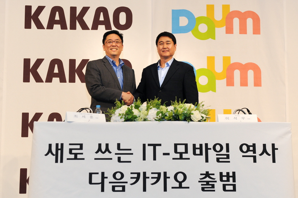 Daum Communications chief executive Choi Sae-hoon (left) and Kakao co-CEO Lee Sir-goo pose at a press meeting where the two sides announced the merger of the Internet portal and mobile messenger firms. (image: Yonhap)