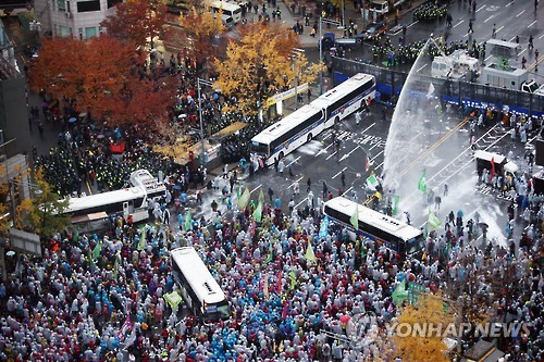 The protest against the government's moves to adopt state history textbooks and its drive for labor reform turned violent as it continued late into the night, with protesters brandishing metal pipes and riot police firing water cannons at them. (Image : Yonhap)