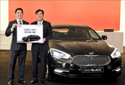 Calvin Kang (L), general manager of Uber Korea, and Cho Yong-won, head of the sales division at Kia Motors, stand by a K9 model ahead of the joint relaunch of UberBlack in Seoul on Nov. 11, 2015. (Image : Uber Korea)