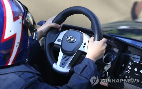 The cars at the playground have an 'auto reset' button which aligns the car with the middle of the track. (Image : Yonhap)