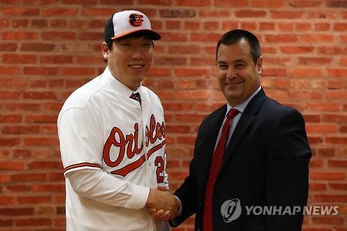 South Korean outfielder Kim Hyun-soo (L) shakes hands with Dan Duquette, executive vice president of baseball operations for the Baltimore Orioles, after signing a two-year, US$7 million deal with the club at Oriole Park in Camden Yards, Baltimore on Dec. 23, 2015. (Image : Leeco Sports Agency)