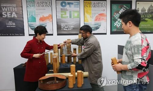 President Park Geun-hye (L) tries out a musical instrument at the new content industry office that opened in Seoul on Dec. 29, 2015. The office is a cluster of venture firms that will be able to receive government consulting services for planning, marketing and managing their content. More than 90 startups are expected to take advantage of the service at the office, which offers working space rent-free for two years. (Image : Yonhap)