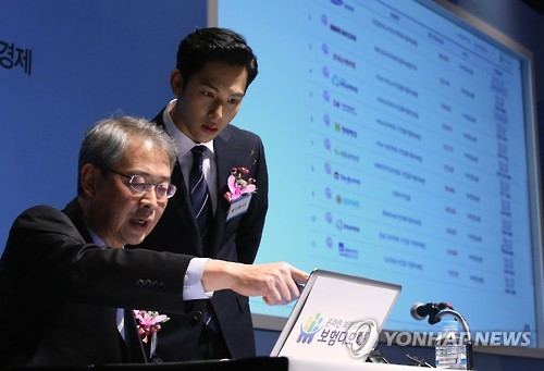 Lim Jong-ryul, (ImChairman of Finance is explaining how to buy insurance through 'Insurance Damoa' to actor and singer Lim Si-wan. (Image : Yonhap)