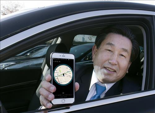 A premium taxi driver poses with a smartphone displaying the Uber application in this photo released by Uber on Jan. 19, 2016. (Image : Uber Technologies Inc.)