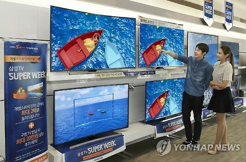 Customers shop for Ultra HD TVs displayed at a showroom in Seoul (Image : Yonhap)