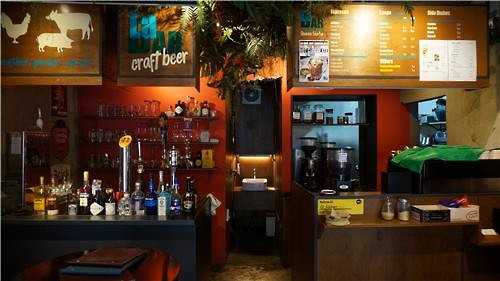 This photo shows a cafe in central Seoul that has two separate tables set up on the right and left each for coffee and beer as it is being shared by two different business owners. (Image : Yonhap)