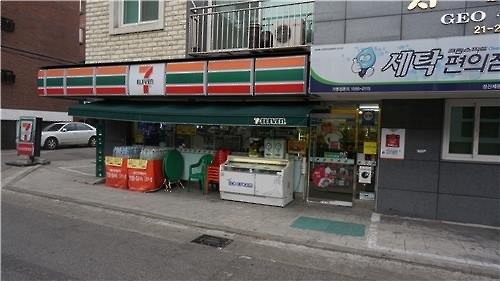 A convenience store located in western Seoul shares space with a dry cleaning shop. (Image : Yonhap)