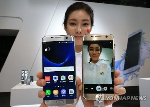 A model poses for a photo with Galaxy S7 smartphones (Image : Yonhap)