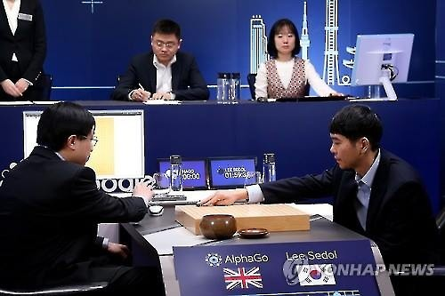 In this photo provided by Google, South Korean Go player Lee Se-dol (R) places his stone against Google's artificial intelligence program AlphaGo during their fifth Go match at the Four Seasons Hotel in Seoul on March 15, 2016. (Image : Yonhap)