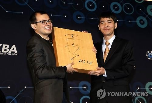 South Korean Go master Lee Se-dol (R) and Google DeepMind CEO Demis Hassabis (L) hold a wooden Go board with Lee's signature at their post-match press conference in Seoul on March 15, 2016. (Image : Yonhap)