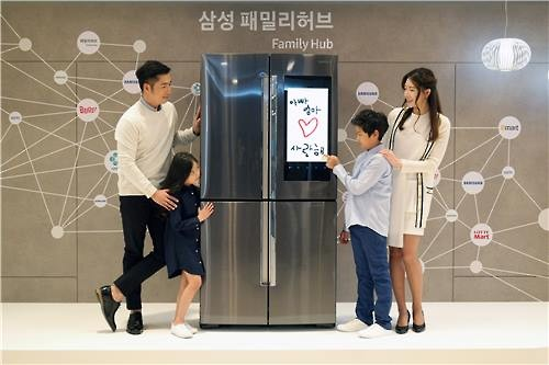 Models pose for a photo with Samsung Electronics Co.'s Family Hub refrigerator at the company's Seoul-based office on March 30, 2016, in this photo released by Samsung. (Image : Yonhap)