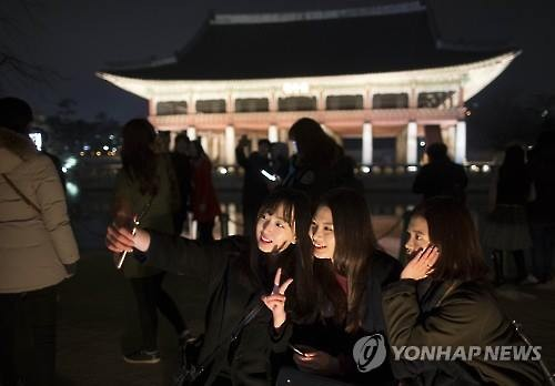 Visitors pose for selfies in front of the Gyeonghoeru Pavilion inside Gyeongbok Palace in Seoul on March 2, 2016. (Image : Yonhap)