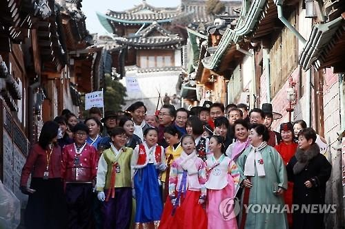 "People wearing traditional Korean clothes, or ""hanbok,"" pose in front of a traditional village in Seoul. (Image : Yonhap)"