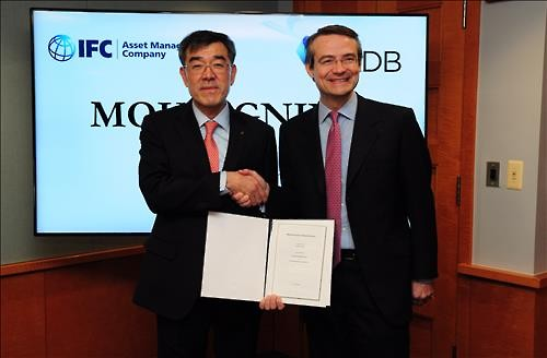 Vice Chairman of the KDB Jun Young-sam (L) and IFC-AMC Chairman Gavin Willson shake hands after signing a memorandum of understanding to establish a partnership between their organizations in Washington on March 2 in this photo provided by the KDB. (Image : Yonhap)