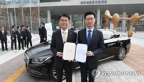 Minister of Land, Infrastructure and Transport Kang Ho-in (L) gives South Korea's first license for a self-driving car to a Hyundai Motor executive in a ceremony in the Sejong Government Complex on March 7, 2016. (Image : Yonhap)