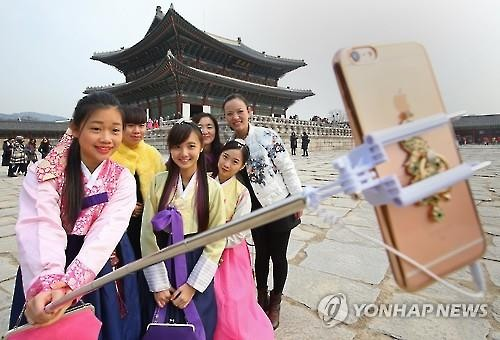 Chinese travelers take a selfie in front of Gyeongbok Palace, a royal place where the kings of the Joseon Kingdom (1932-1910) resided and administered state affairs, in downtown Seoul. (Image : Yonhap)