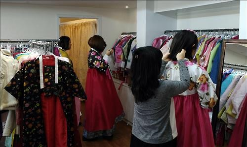 Young girls try on hanbok at a local hanbok rental shop in Seoul on March 17, 2016. (Image : Yonhap)