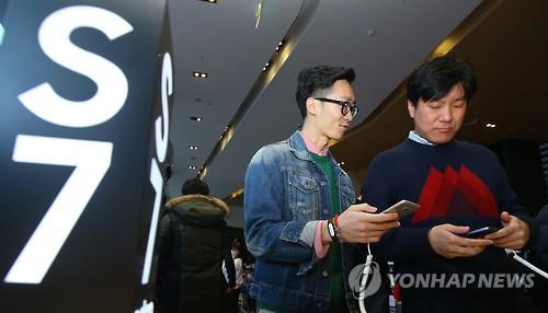 Visitors test the Galaxy S7 smartphones at a Seoul-based shop. (Image : Yonhap)