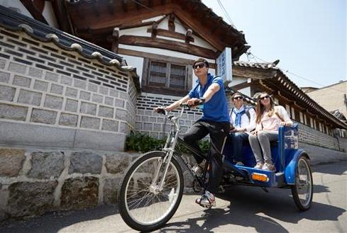 This photo released by the Korea Tourism Organization on April 12, 2016, shows foreign visitors enjoying a pedicab ride in a traditional hanok village in Seoul. (Image : Yonhap)