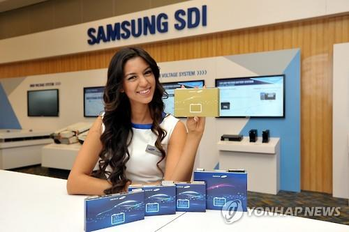 A model, in this photo provided by Samsung SDI Co., poses with the company's new electric vehicle battery cells at an auto show held in the United States in January 2016. (Image : Yonhap)