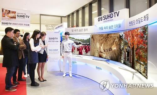 Shoppers look at Samsung TVs on display at a Seoul department store. (Image : Yonhap)