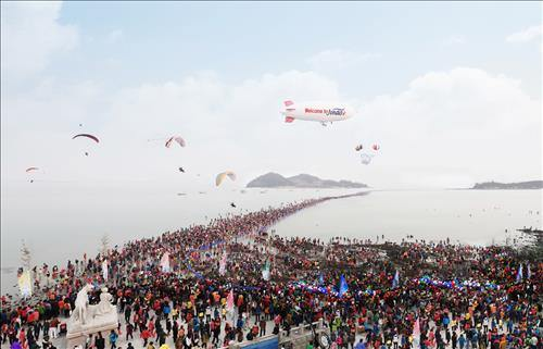 The undated file photo, released by the Municipality of Jindo, shows tourists crowding the southern beach in Hoedong-ri, Gogun-myeon, Jindo-gun, South Jeolla Province, to watch the seawaters part at the Jindo Sea-Parting Festival. (Image : Yonhap)