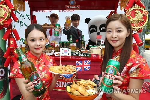 Models pose for a photo with Tsingtao products. (Image : Yonhap)