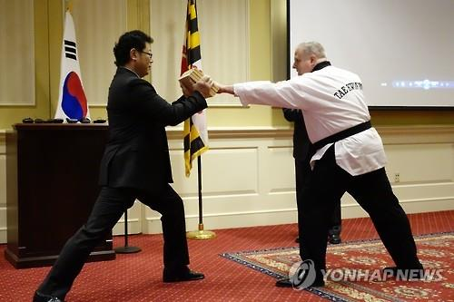 "Maryland Gov. Larry Hogan attempts to break wooden boards during a ceremony held at the Maryland Miller Senate Office Building to declare ""Taekwondo Day"" on April 5. (Image : Yonhap)"