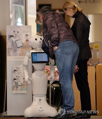 "An artificial intelligence robot named ""Pepper"" greets visitors at the entrance of a mobile shop in Tokyo. (Yonhap file photo)"